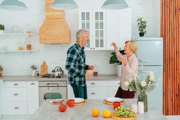 Marido e mulher dançam na cozinha durante o café da manhã
