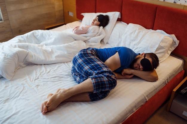 Marido e mulher dormem separados na cama, relacionamento ruim