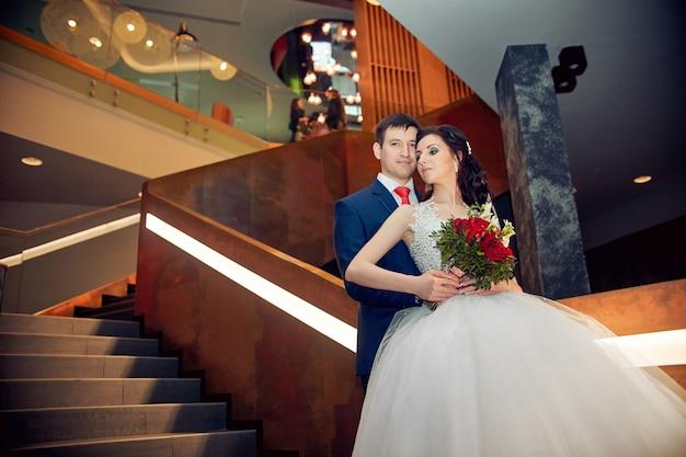 Marido e mulher em pé na escada se abraçando