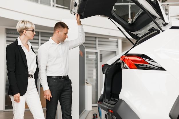 Marido e mulher escolher um carro na concessionária.