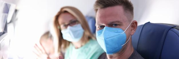 Marido e mulher estão voando no avião usando máscaras médicas