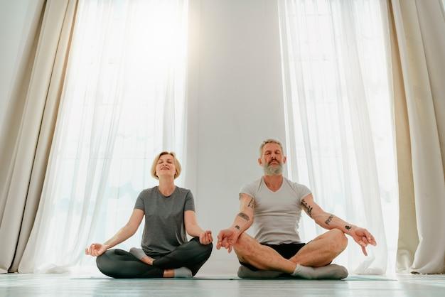 Marido e mulher fazem exercícios de ioga juntos em casa