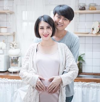 Marido e mulher grávida de mãos dadas em forma de coração na barriga de mulher