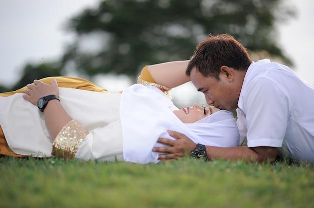Marido e mulher grávida deitada na grama e o marido beijam a testa da esposa.