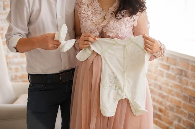 Marido e mulher grávida segurando roupas de bebê e botinhas
