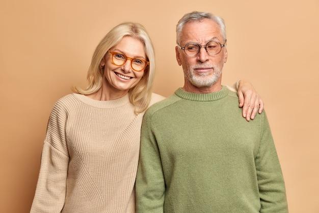 Marido e mulher idosos posam para retrato de família se abraçando, sorrindo positivamente vestidos com macacões de óculos, apoiados na parede marrom do estúdio