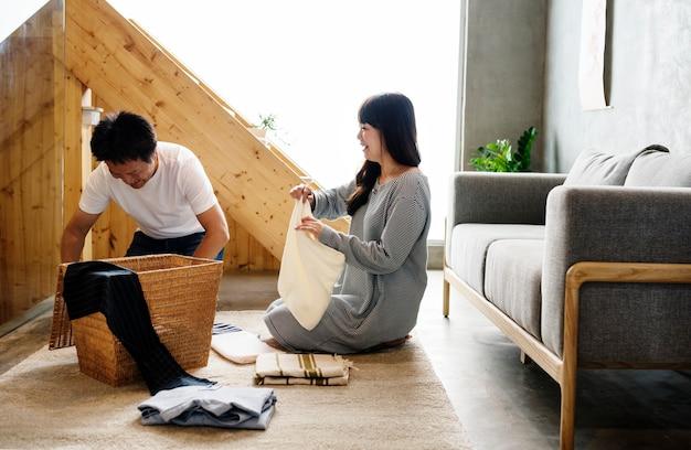 Marido e mulher japoneses dobrando roupas juntos