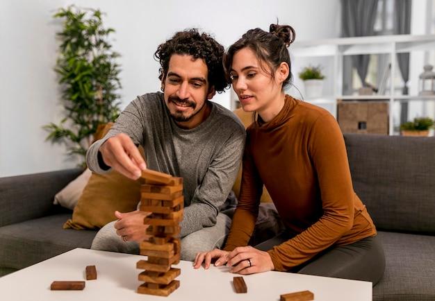Marido e mulher jogando um jogo de torre de madeira dentro de casa