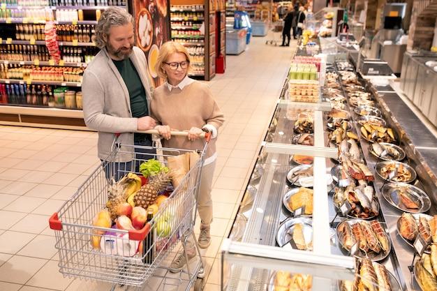 Marido e mulher maduros empurrando o carrinho de compras com produtos alimentícios frescos enquanto se movem ao longo de uma grande vitrine com frutos do mar no supermercado