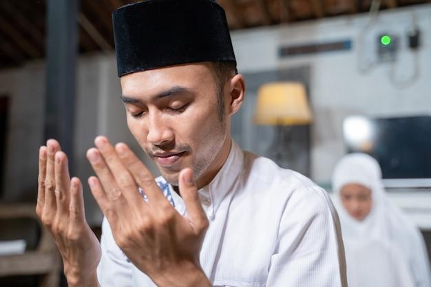 Marido e mulher muçulmanos asiáticos rezando jamaah juntos em casa