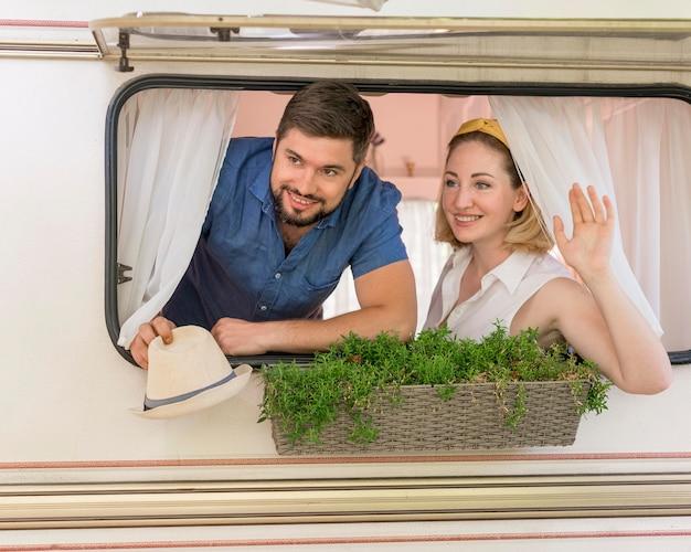 Marido e mulher olhando pela janela de um trailer