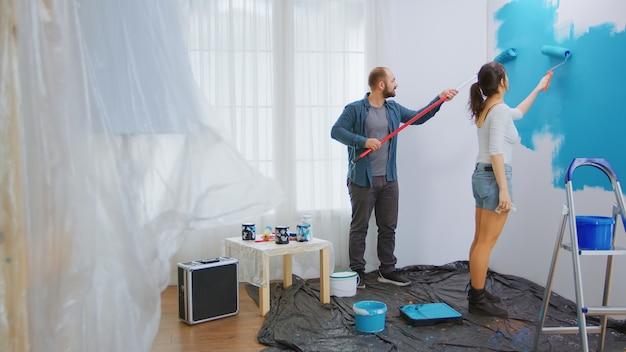 Marido e mulher pintando a parede da sala com escova de rolo. renovação de apartamento familiar, reforma, feliz. redecoração de apartamento e construção de casa durante a reforma e melhoria. reparação e descompressão