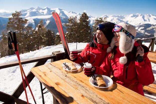 Marido e mulher relaxam depois de esquiar se divertindo na estação de esqui