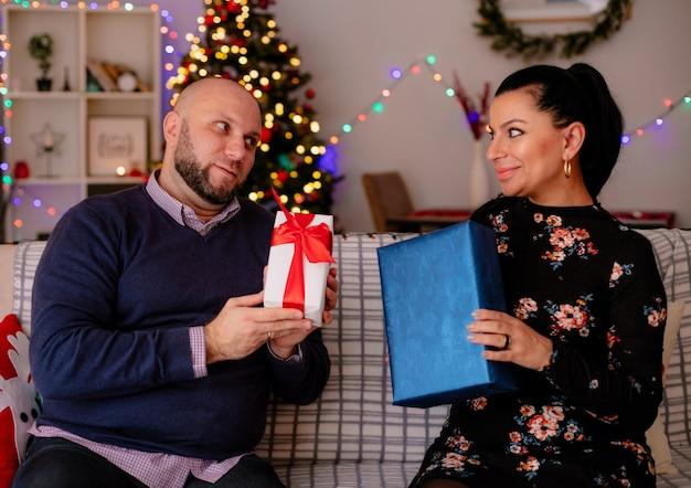 Marido e mulher satisfeitos em casa na época do natal, sentados no sofá da sala, ambos segurando um pacote de presente, olhando um para o outro