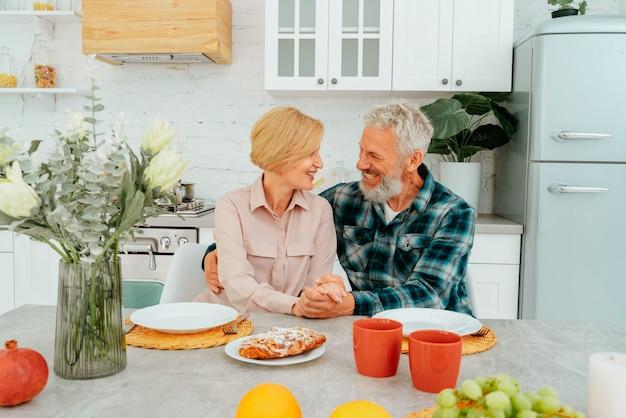 Marido e mulher se abraçando em casa durante o café da manhã