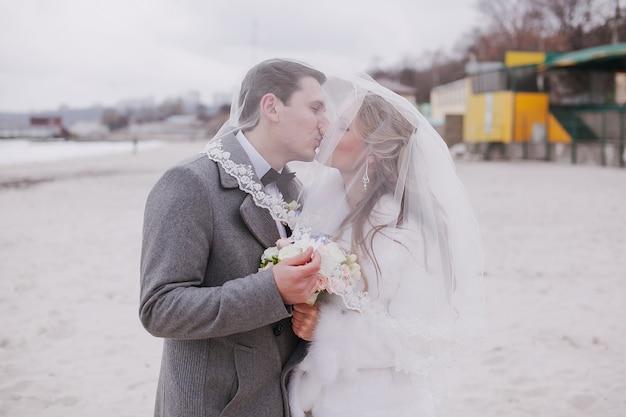 Marido e mulher se beijando sob o véu