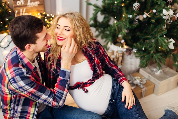 Marido e mulher se divertem na árvore de natal