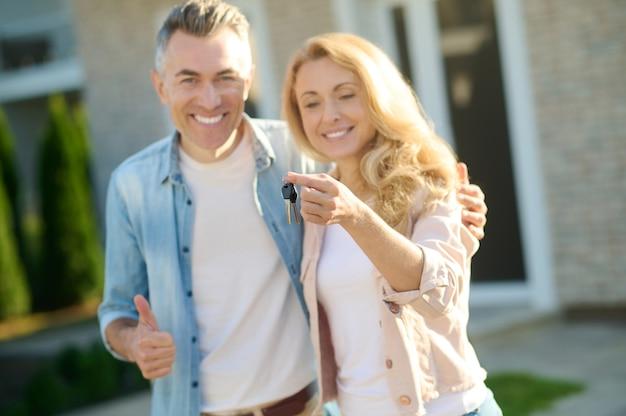 Marido e mulher sorridentes com a casa das chaves