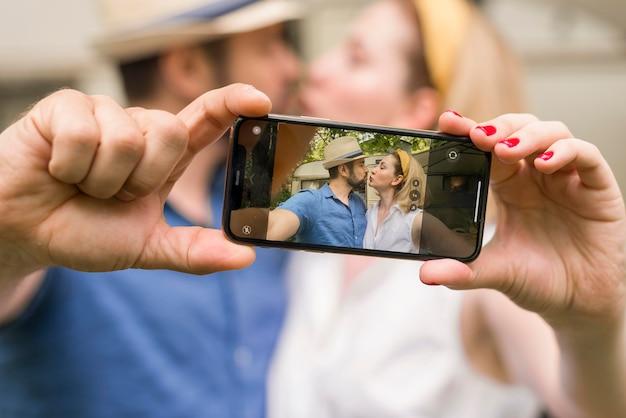 Marido e mulher tirando uma selfie enquanto se beijam