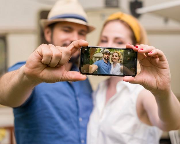 Marido e mulher tirando uma selfie juntos em uma viagem