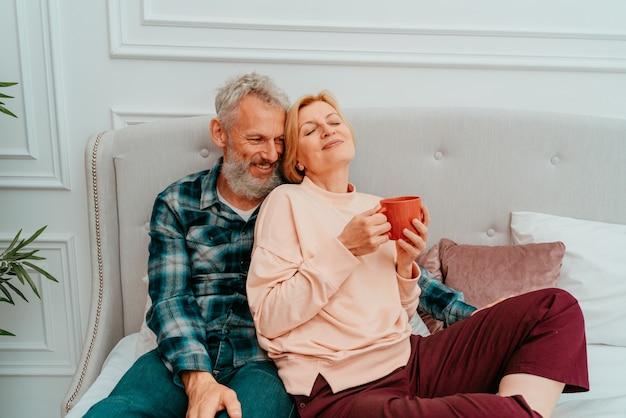 Marido e mulher tomam café da manhã com café na cama em casa