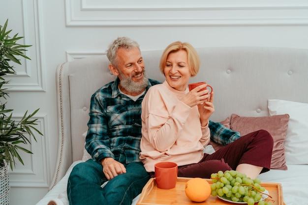 Marido e mulher tomam café da manhã na cama com café e frutas