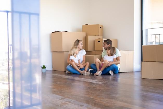 Marido, esposa e suas filhas sentados no chão e se mudando para uma nova casa