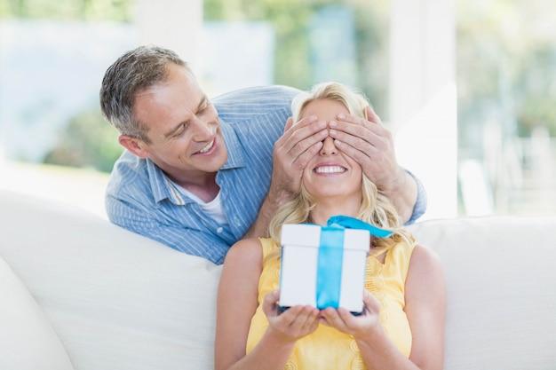 Marido esposa surpreendente com um presente na sala de estar