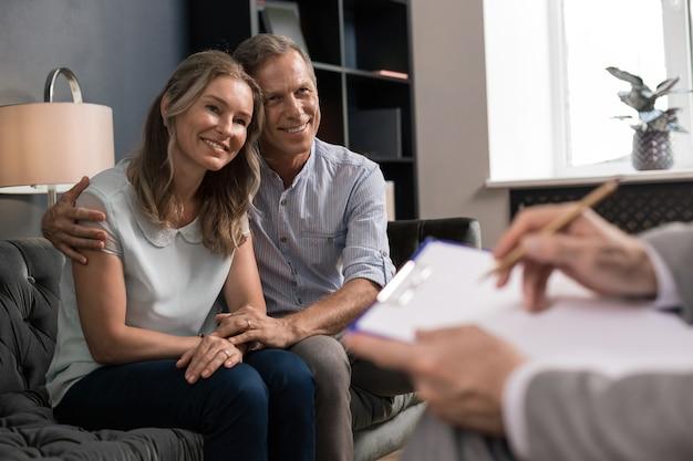 Marido feliz abraçando sua esposa sorridente enquanto está sentado no sofá na frente de um psicanalista