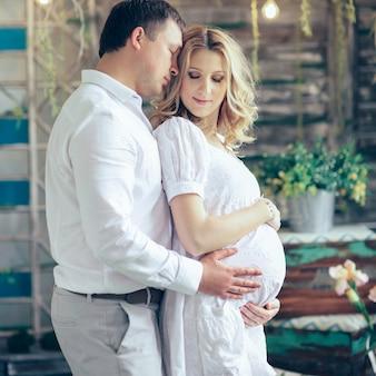 Marido feliz e esposa grávida em um café, abraçando ternamente e segurando a barriga