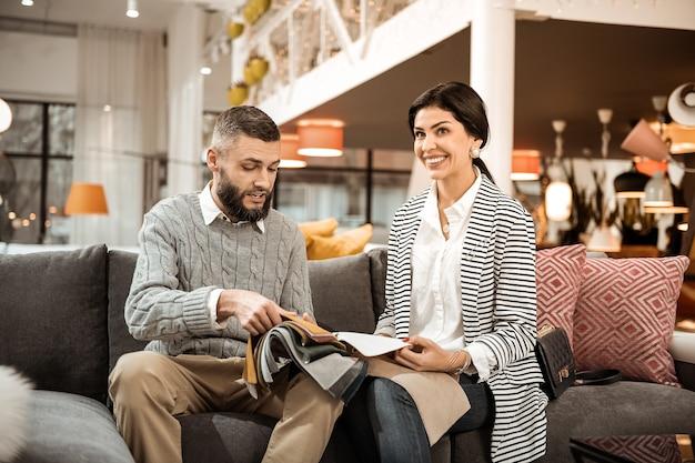 Marido folheando. casal adulto positivo apreciando o processo de escolha de móveis enquanto está sentado no sofá da loja