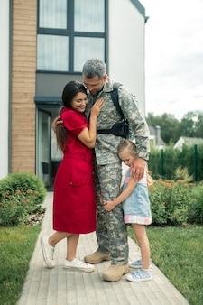 Marido forte e heróico. mulher de cabelos escuros usando um vestido vermelho em pé perto de seu heróico marido e filha