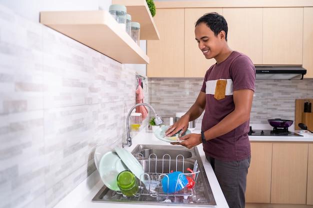 Marido lavar prato na pia da cozinha