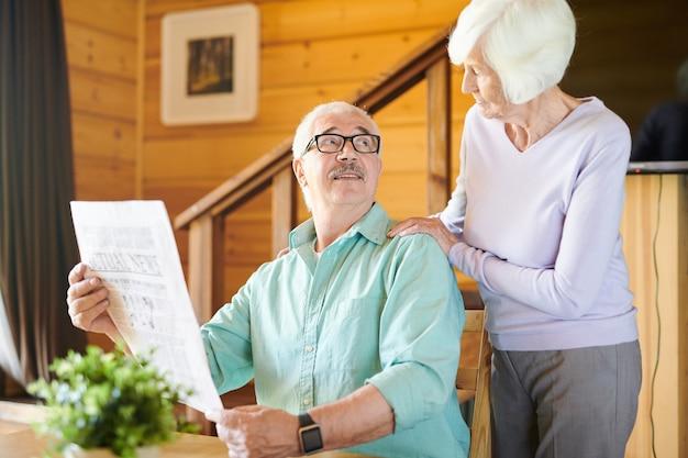 Marido maduro em trajes casuais e óculos olhando para a esposa durante uma conversa enquanto está sentado à mesa lendo notícias