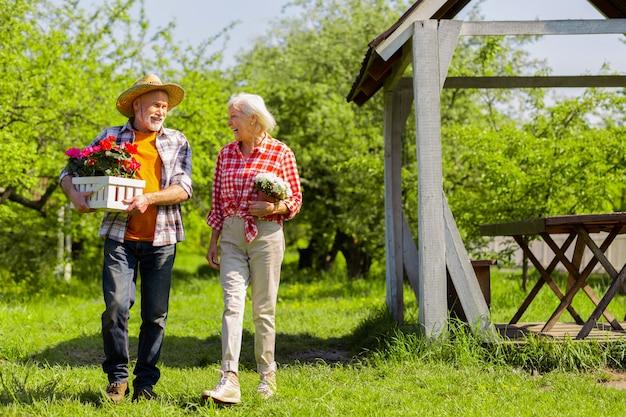 Marido prestativo. caixa de cuidados prestativa para marido barbudo com vasos de flores andando perto de sua esposa