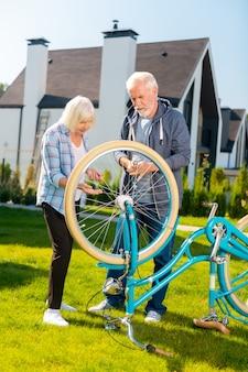 Marido prestativo. marido barbudo amoroso e prestativo consertando a velha bicicleta azul de sua atraente esposa loira