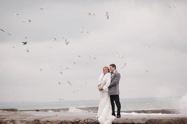 Marido que abraça sua esposa no porto