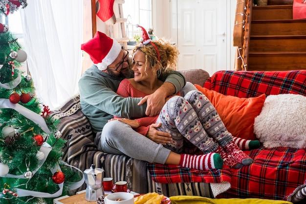 Marido romântico abraçando sua esposa enquanto está sentado no sofá da sala durante a celebração do natal em casa. casal de chapéu e meias com árvore de natal decorada.
