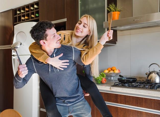 Marido segurando a concha e a espátula na mão carregando sua esposa nas costas