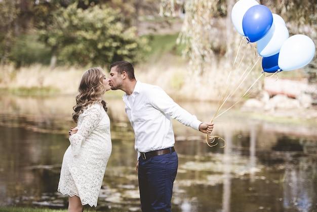 Marido segurando balões e beijando a esposa grávida em um jardim com lago