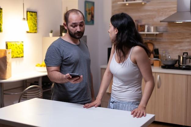 Marido segurando smartphone da esposa com mensagens secretas
