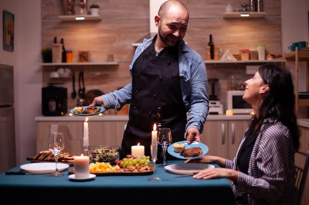 Marido servindo a esposa com comida saborosa durante a celebração do relacionamento na cozinha. homem preparando um jantar festivo com comida saudável, cozinhando um jantar romântico para sua mulher,