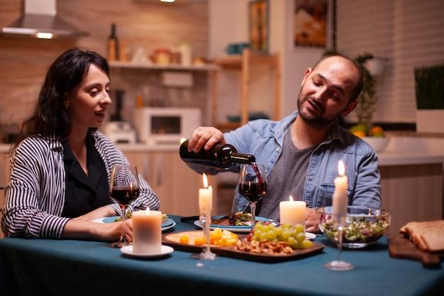 Marido servindo esposa a esposa durante um jantar romântico na sala de jantar. jovem servindo vinho tinto no copo da esposa. casal feliz caucasiano romântico sentado à mesa comemorando.