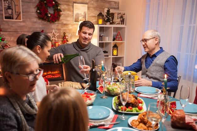 Marido servindo vinho para o sogro na celebração do natal. família feliz