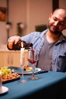 Marido servindo vinho tinto no copo, celebrando o relacionamento com a esposa na sala de jantar. jovem servindo vinho tinto no copo da esposa. casal feliz caucasiano romântico sentado à mesa comemorando.
