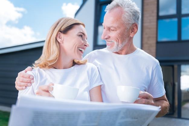 Marido solidário. mulher sorridente e atraente olhando para o marido barbudo que apoiava enquanto estava do lado de fora da casa