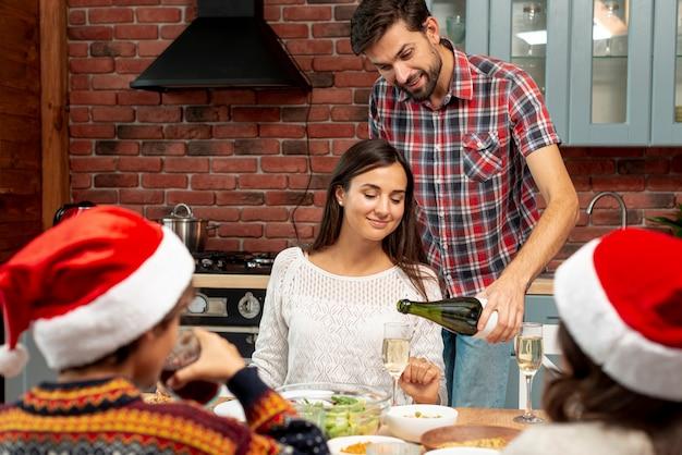Marido tiro médio, derramando champanhe para sua esposa