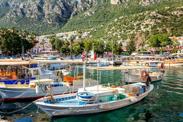 Marina com barcos de pesca e iates em uma cidade ensolarada.