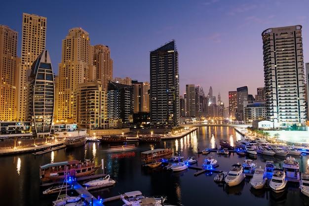 Marina dubai, com, barcos, e, edifícios, à noite, emirates árabes unidos