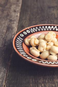 Marinado, cogumelos em conserva champignon em tigela marrom na madeira.
